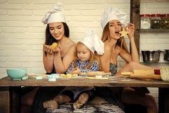 Famille heureuse et concept d'enfance Frère et soeurs dans des chapeaux de chef préparant des biscuits Photographie stock libre de droits