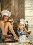 Famille heureuse et concept de jour de mères Femme et garçon dans des chapeaux de chef dans la cuisine Images libres de droits
