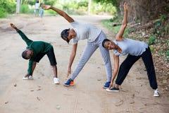 Famille heureuse exerçant ensemble l'étirage au sport en plein air photo libre de droits