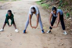 Famille heureuse exer?ant ensemble l'?tirage au sport en plein air photos libres de droits