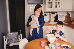 Famille heureuse faisant cuire au four ensemble dans la cuisine blanche moderne Fille de mère, de fils et de bébé faisant cuire d Images stock