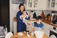 Famille heureuse faisant cuire au four ensemble dans la cuisine blanche moderne Fille de mère, de fils et de bébé faisant cuire d Image libre de droits