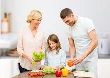 Famille heureuse faisant cuire la salade végétale pour le dîner Photo libre de droits