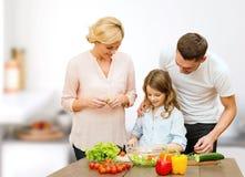 Famille heureuse faisant cuire la salade végétale pour le dîner Images libres de droits