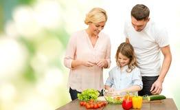 Famille heureuse faisant cuire la salade végétale pour le dîner Photo stock