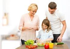 Famille heureuse faisant cuire la salade végétale pour le dîner Photos stock