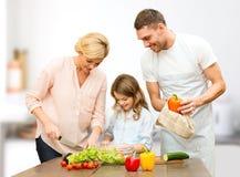 Famille heureuse faisant cuire la salade végétale pour le dîner Photos libres de droits
