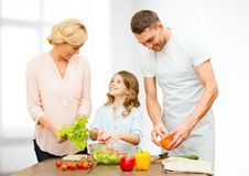 Famille heureuse faisant cuire la salade végétale pour le dîner Images stock