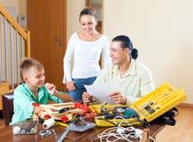 Famille heureuse faisant ensemble quelque chose avec des outils de travail Photographie stock