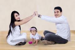 Famille heureuse faisant le signe à la maison à la maison Photos stock