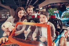 Famille heureuse, fils ravi s'asseyant sur la voiture de jouet photo stock