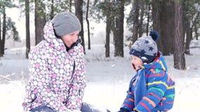 Famille heureuse : jeu de maman et de fils en jetant la neige dans une forêt ou un parc couverte de neige d'hiver Émotions d'expé banque de vidéos