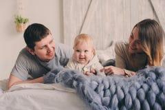 Famille heureuse jouant à la maison sur le lit Capture de mode de vie de mère, de père et de bébé Photo libre de droits