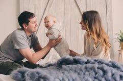 Famille heureuse jouant à la maison sur le lit Capture de mode de vie de mère, de père et de bébé Image libre de droits