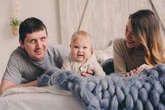 Famille heureuse jouant à la maison sur le lit Capture de mode de vie de mère, de père et de bébé Images libres de droits