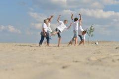 Famille heureuse jouant au football sur une plage dans le jour d'été photo stock