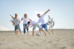 Famille heureuse jouant au football sur une plage dans le jour d'été photographie stock