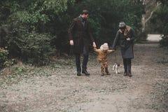 Famille heureuse jouant avec le terrier de renard de chien extérieur Photographie stock