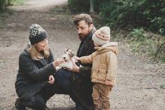 Famille heureuse jouant avec le terrier de renard de chien extérieur Images libres de droits