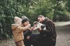 Famille heureuse jouant avec le terrier de renard de chien extérieur Photo stock