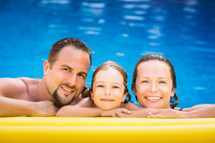 Famille heureuse jouant dans la piscine Photos stock