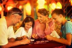 Famille heureuse jouant des cartes Photographie stock