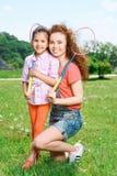 Famille heureuse jouant le badminton Images stock