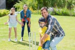 Famille heureuse jouant le cricket ensemble image stock