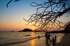 Famille heureuse jouant sur la plage au temps de coucher du soleil Image stock