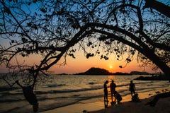 Famille heureuse jouant sur la plage au temps de coucher du soleil Photo stock