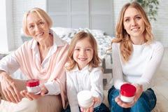 Famille heureuse joyeuse te montrant des bouteilles de crème image libre de droits