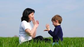 Famille heureuse : la mère et l'enfant s'asseyent sur l'herbe verte et le jeu, se giflant sur Batty banque de vidéos