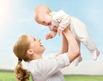 Famille heureuse. La mère jette vers le haut le bébé dans le ciel Photos stock