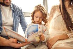 famille heureuse lisant un livre à sa fille la fleur de jour donne à des mères le fils de momie à Photographie stock