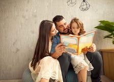 famille heureuse lisant un livre à sa fille la fleur de jour donne à des mères le fils de momie à Photo libre de droits