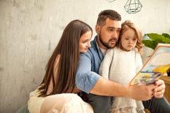 famille heureuse lisant un livre à sa fille la fleur de jour donne à des mères le fils de momie à Image libre de droits
