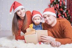 Famille heureuse lisant un livre avec le conte de fées de Noël Photo stock