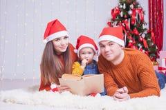 Famille heureuse lisant un livre avec le conte de fées de Noël Photographie stock