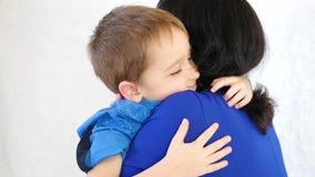 Famille heureuse : mère et bébé étreignant au-dessus du fond blanc banque de vidéos