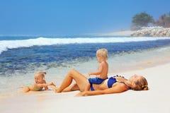 Famille heureuse - mère, fils de bébé, fille prenant un bain de soleil sur la plage de mer Photos libres de droits