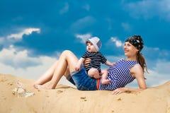 Famille heureuse, maman et petit fils dans des gilets rayés ayant l'amusement dedans Photographie stock libre de droits