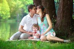 Famille heureuse, maman, papa et petit fils ayant l'amusement dans le parc dessus Photo libre de droits