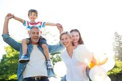 Famille heureuse marchant au parc Photos libres de droits