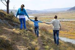 Famille heureuse marchant dans les montagnes Photographie stock