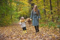 Famille heureuse marchant en parc d'automne - la mère, sa fille et ours de nounours de jouet parmi les feuilles jaunes Image stock