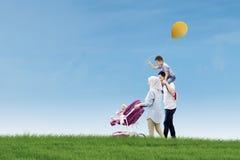 Famille heureuse marchant ensemble dans le pré Image libre de droits