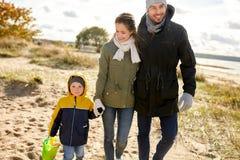 Famille heureuse marchant le long de la plage d'automne photographie stock