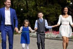 Famille heureuse marchant le long de la rue suburbaine Photographie stock libre de droits