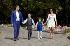 Famille heureuse marchant le long de la rue suburbaine Photos libres de droits