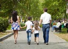 Famille heureuse marchant le long de la rue suburbaine Photographie stock